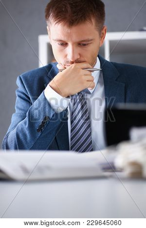 Serious Businessman In The Office Examines Documents With Infographics Performing Assigned Work Hold