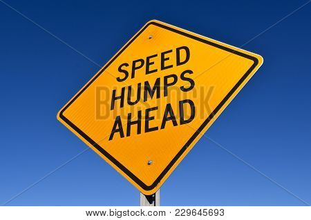 Signs Warning Of Speed Humps Ahead Against A Blue Sky