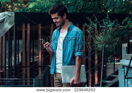 You Have One Unread Message. Handsome Young Man Carrying His Laptop And Using His Smartphone With Sm