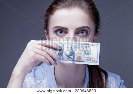 Business Woman Covering Her Mouth With A Dollar Banknote As Symbol Of Bribery, Cheating, Financia An
