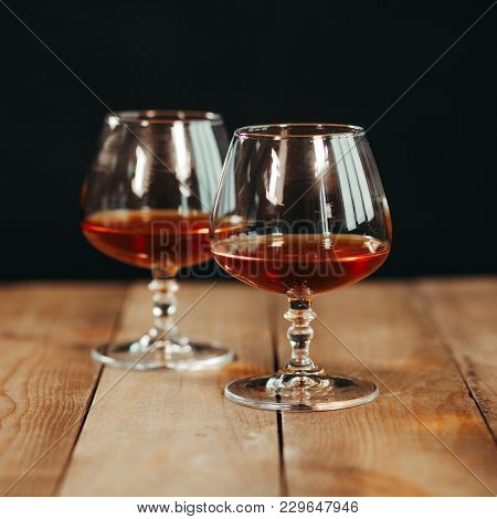Close Up Of Two Glass Goblets With Alcohol Resting On A Wooden Table Against A Dark Background.