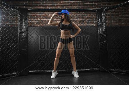 A Beautiful Sporty Sexy Slender Brunette Is Standing In The Gym. A Fitness Bikini Model Wears Sports
