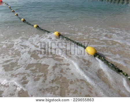 A Row Of Yellow Buoy Markers On A Sandy Beach. Dubai. 2018