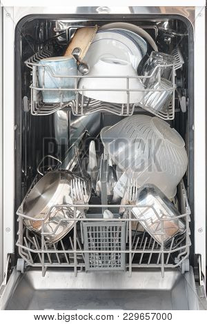 Dirty Dishes In A Narrow Dishwasher, Ready For Cleaning, Selected Focus,  Narrow Depth Of Field