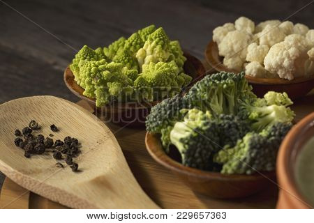 High Angle View Of Fresh Broccoli, Romanesco Broccoli And Cauliflower On A Wooden Cutting Board. Foc