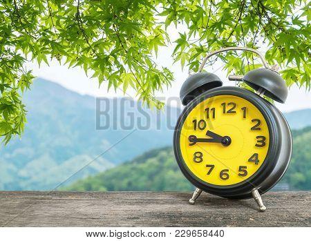 Closeup Black And Yellow Alarm Clock For Decorate Show A Quarter To Nine O C'clock Or 8:45 A.m. On B