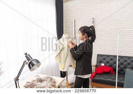 Smiling Young Asian Designer Tailor A Dress Working On Her Designs In The Studio Near Mannequin In O