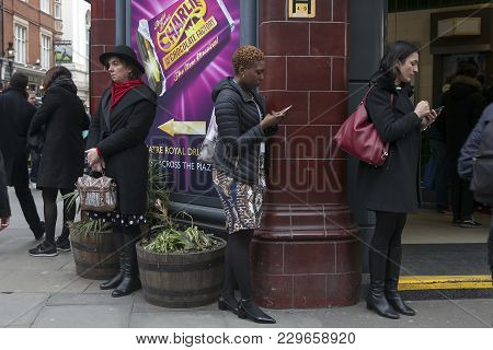 London - September 27, 2016: Women Buried In The Phone, Waiting For The Subway Around Covent Garden