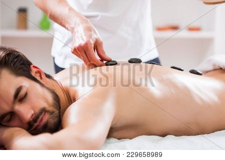 Young Man Is Enjoying Massage On Spa Treatment.