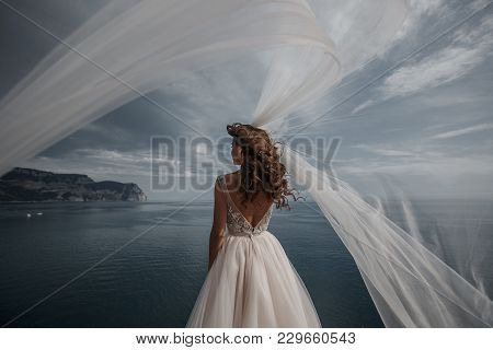 Beautiful Bride Stands On A Cliff Above The Sea In A Glamorous White Wedding Dress View Of Veil.roma