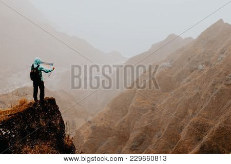 Hiker With Map In Steep Rocky Terrain In Front Of A Incredible Panorama View Of High Mountain Ranges