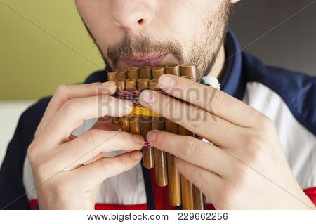 Bearded White Male Musician Blowing A Traditional Pan Flute, Wind Music, Musicology, Music Education