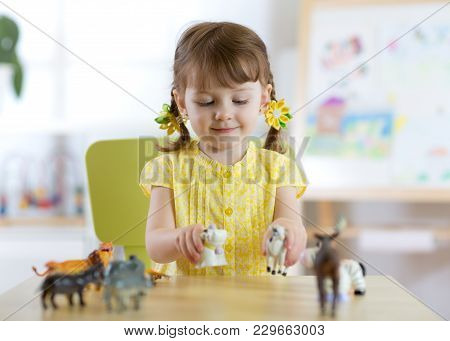 Happy Little Kid Girl Plays Zoo At Home Or Daycare Centre