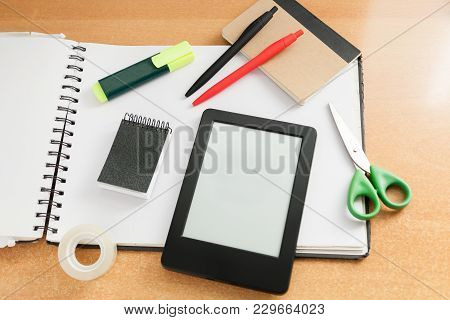 E-reader With Nothing On Screen With Various Office Items Like Scissors, Scotch Tape, Note Blocks, M