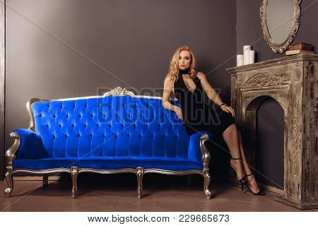 Young Woman In Black Dress Is Sitting On The Blue Couch Near The Fireplace