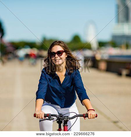 Urban biking - young woman and bike in city