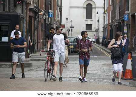 London, Uk - August 27, 2016: Men In Shorts And A Woman In A Dress Cross The Road Near Brick Lane