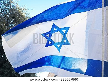 Israel Flag. White And Blue Colors. Israel Flag Waving Against Sky