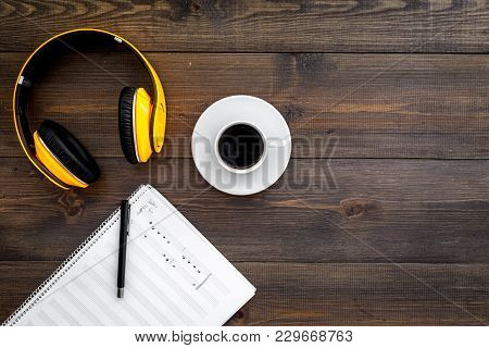 Work Desk Of Modern Composer. Music Notes Near Headphones And Coffee On Dark Wooden Background Top V