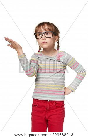What Is This. Indignant Puzzled Child Girl Gestures With Hand, Pursing Lips, Frowns Face In Dissatis