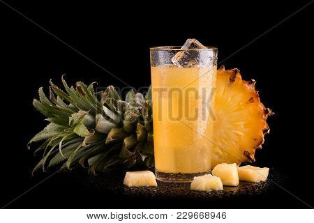 Fresh Chilled Pineapple Juice With Ice. Chilled Ananza Juice With Ice And Pieces Of Fruit On A Black