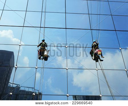 Workers Washing Windows Of The Modern Skyscraper Office Building.