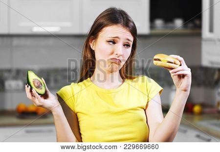 Attractive Long-haired Woman Hesitating Between Fresh Avocado And Unhealthy Hamburger, Decides To Ha