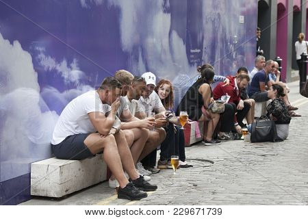 London, England - July 12, 2016 People Sit On The Street Near The Pub, Drinking Beer And Smoking