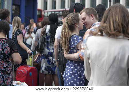 London, England - July 12, 2016 Young Loving Couple Embracing And Kissing At Rush Hour Near The Metr