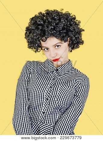 Young Woman With Afro-hair Looks Embarrassed And Mistrustfully Into The Camera, Isolated On Yellow
