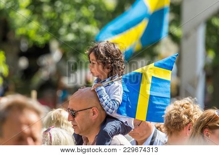 Jakobsberg, Sweden - June 6, 2017:  Profile View Of A Little Girl Sitting On A Mans Shoulder Holding