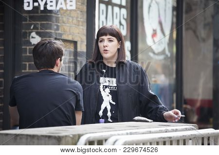 London, England - July 12, 2016 Girl In Black Coat Sitting At The Table At Restaurant
