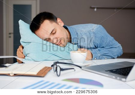 Stressful Male Sleeping On The Table With Laptop And Documents. Sleepworking After Long Junkets Of E