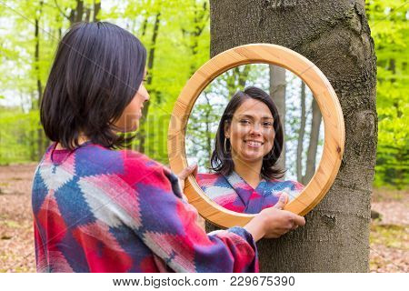 Young Colombian Woman Looking At Mirror In Spring Forest