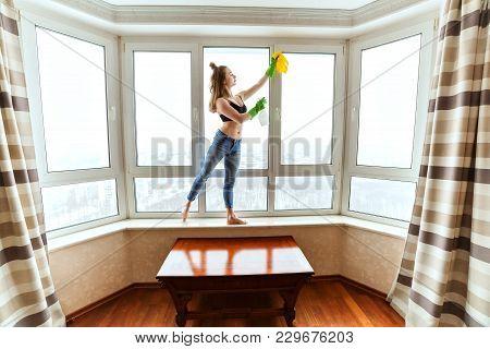 Young Woman Is Washing Windows, She Has A Slim Figure.