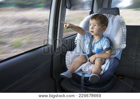 Cute Little Boy Observing The Countryside From His Car Safety Seat. He Is Pointing Something