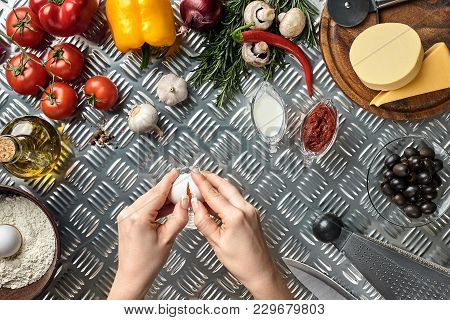 Set Of Ingredients For Pizza And Baker's Hand Smash Eggs On Metal Table