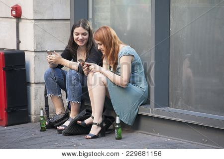London, England - August 25 , 2016 Two Smiling Girl Friends Sitting On A Windowsill Near The Store,