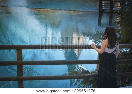 Attractive Woman Looking Towards The Lake - Back View Of A Brunette Young Woman, Dressed Elegantly I