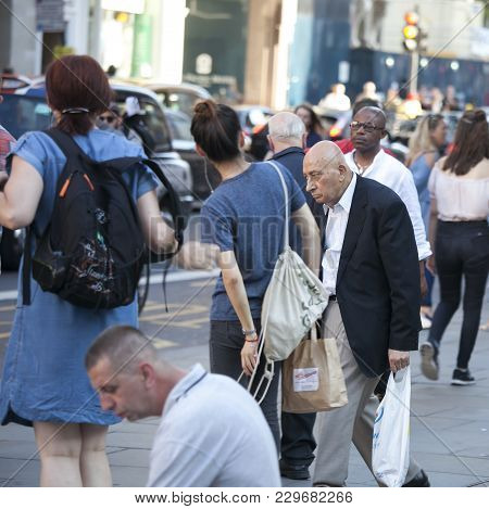 London, England - August 25 , 2016 An Elderly Stooped Man Walking Down The Street Through The Crowd