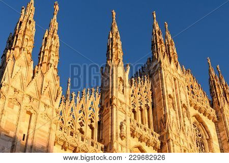 Low Angle View Of The Sunlit Facade Of Milan Iconic Gothic Cathedral Or Duomo Di Milano At Dusk, Fro
