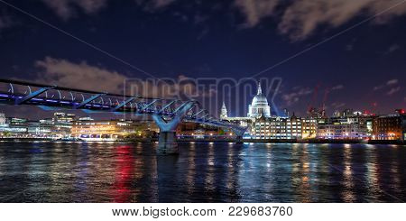 St Paul's Cathedral , the river Thames and the Millennium Bridge at night. London cityscape, showing illuminated bars and restaurants along the riverbank. Panoramic view