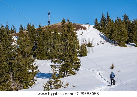 Male Hiker With Blue Jacket And Backbag Walking With Black Dog Through Deep Snow To Summit Of Mounta