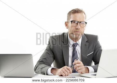 Portrait Of A Middle Aged Investment Advisor Businessman Using Mobile Phone And Laptop While Working