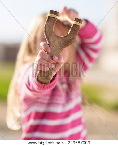 Small Girl Aiming With A Sling Shot, Outdoors