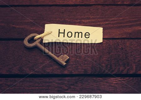 Key And Keyring With The Word Home Over Dark Wooden Table