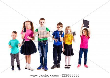The Little Boys And Girls In Colorful Clothes Standing With Gadgets Isolated On A White Background.