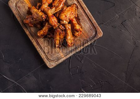 Fried Chicken Wings In Soy And Honey Sauce On The Wooden Board On The Black Table