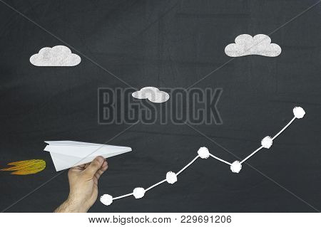 Man Holding Paper Plane Flying Up On Growing Graph Arrow Chart On Chalkboard. Business Finance Conce