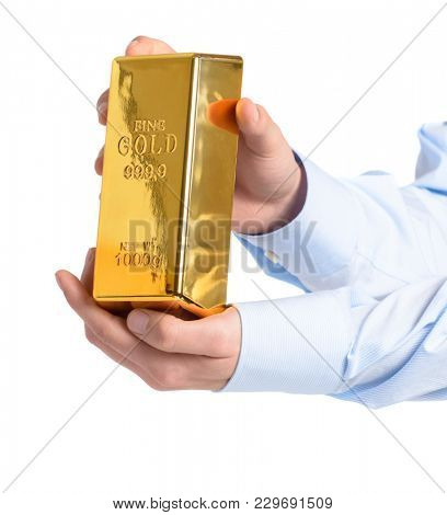Close-up Of Hand Holding Gold Bar Over White Background